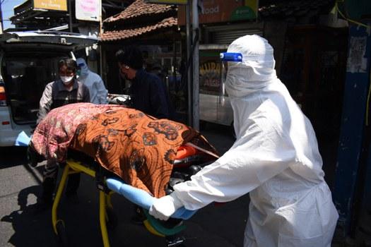 Petugas kesehatan membawa jenazah penderita COVID-19 yang meninggal saat melakukan isolasi mandiri di rumahnya di Bandung, 28 Juli 2021. [AFP]