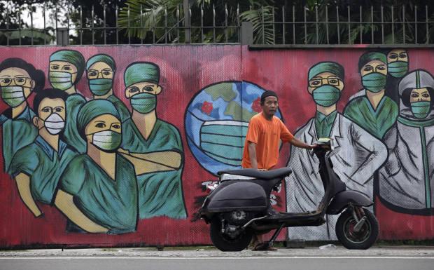 Dalam foto tertanggal 15 April 2020 ini, seorang lelaki dengan kendaraan bermotornya berdiri di depan sebuah mural yang dibuat untuk menghormati para tenaga kesehatan yang telah banyak berjatuhan dalam penanganan pandemi COVID-19. (AP)