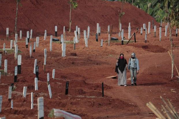 Dua perempuan berjalan di pemakaman Pondok Ranggon yang kembali membuka lahan baru untuk mengakomodasi meningkatnya angka kematian akibat COVID-19 di Jakarta, 24 September 2020.