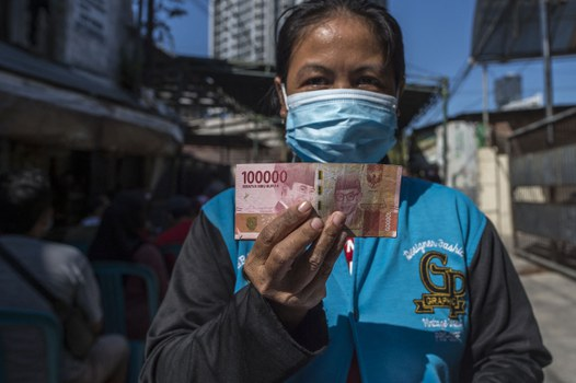 Seorang perempuan memperlihatkan uang tunai yang diberikan oleh pemerintah kepada warga yang tidak mampu secara ekonomi akibat pandemi COVID-19, di Surabaya pada 19 Juli 2021. [Foto: AFP]