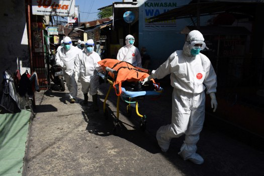 Petugas kesehatan mengevakuasi jenazah korban COVID-19 yang meninggal saat menjalani isolasi mandiri di rumahnya karena penuhnya rumah sakit, di Bandung pada 18 Juli 2021. [AFP]