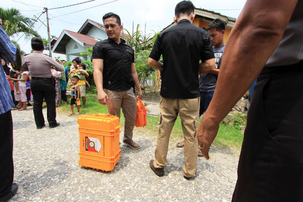 Polisi membawa barang bukti yang telah dimasukkan dalam kotak dari lokasi penggeledahan rumah terduga teroris di Kabupaten Kampar, Riau, 24 Oktober 2017. (Dina Febriastuti/BeritaBenar)