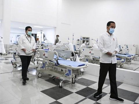"""Presiden Joko """"Jokowi"""" Widodo dan Menteri Badan Usaha Milik Negara (BUMN) Erick Thohir mengecek peralatan medis di Rumah Sakit Darurat COVID-19 yang tadinya merupakan Wisma Atlet Asian Games di Jakarta, Senin (23/3/2020)."""