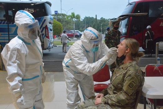 Petugas kesehatan melakukan tes COVID-19 kepada seorang anggota pasukan militer AS yang baru tiba di Bandara Sultan Mahmud Badaruddin II Palembang, Sumatra Selatan, 24 Juli 2021. (Dinas Penerangan TNI AD)