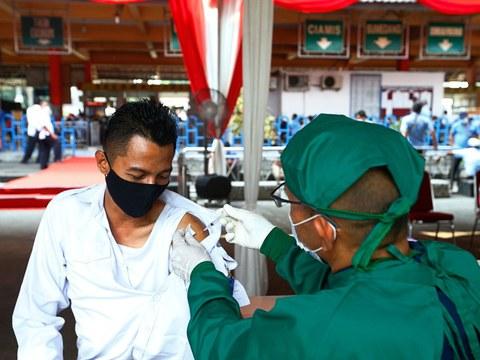 Seorang warga menerima suntikan vaksin COVID-19 dari AstraZeneca dalam program vaksin massal untuk para pekerja transportasi di Stasiun Bus Kampung Rambutan di Jakarta, 11 Juni 2021.