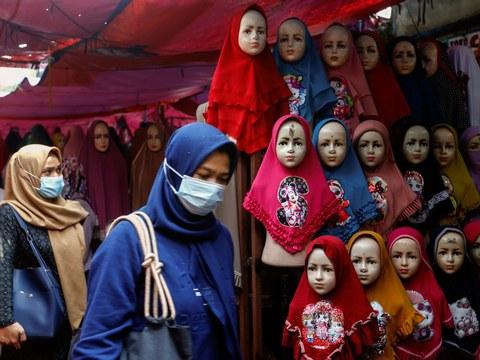 Dua perempuan melintasi kios yang menjual jilbab di Pasar Tanah Abang, Jakarta, 16 Maret 2021.