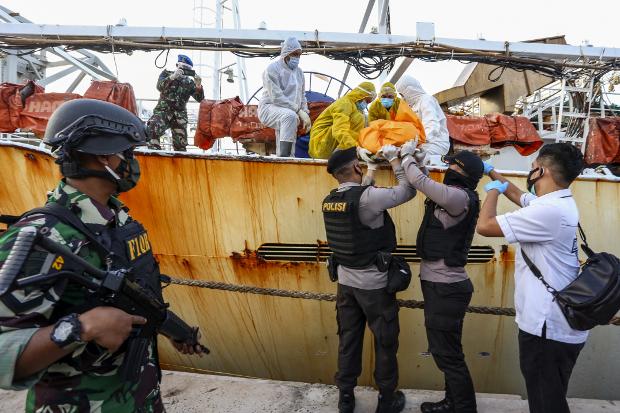 Dalam foto tertanggal 8 Juli 2020 ini, petugas menurunkan seorang mayat pekerja asal Indonesia yang meninggal saat bekerja di kapal penangkap ikan Cina, setelah kapal tersebut ditangkap di wilayah Batam, Kepulauan Riau. [AFP]