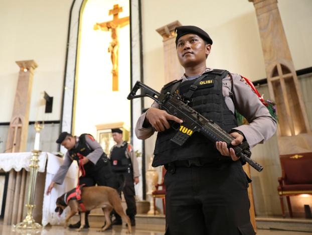 Seorang polisi berjaga-jaga ketika tim penjinak bom membawa seekor anjing pelacak saat melakukan penyisiran menjelang libur Natal di Gereja Katolik The Good Shepherd di Surabaya, Indonesia, Senin, 23 Desember 2019. [AP]