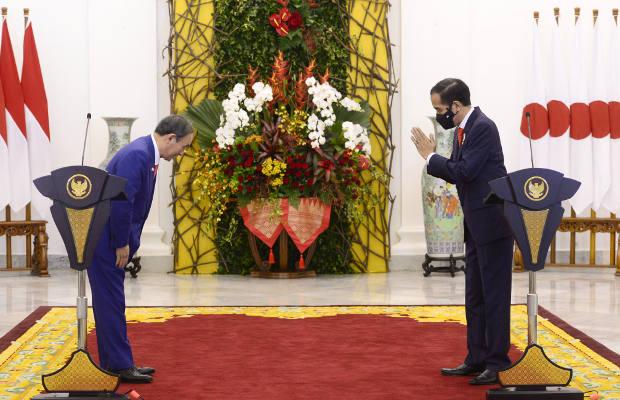 Perdana Menteri Jepang Yoshihide Suga (kiri) dan Presiden Indonesia Joko Widodo saling memberikan salam dalam  konferensi pers bersama di Istana Kepresidenan RI, di Bogor, 20 Oktober 2020. [Foto: Istana Kepresidenan RI]