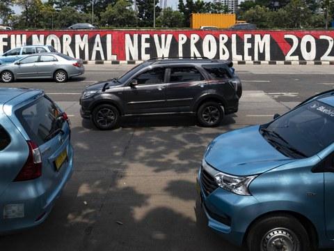Kendaraan melewati tembok yang bertuliskan kata-kata merujuk pada keadaan baru pasca pelonggaran Pembatasan Sosial Berskala Besar (PSBB) di tengah wabah COVID-19 yang belum berakhir, di Jakarta, 10 Juni 2020.