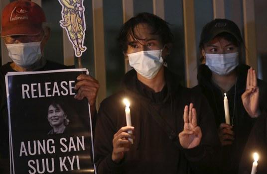 Aktivis menunjukkan simbol perlawanan tiga jari memprotes kudeta militer di Myanmar, di luar Sekretariat ASEAN di Jakarta 12 Maret 2021. [AP]