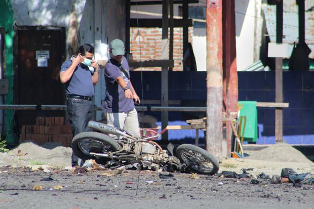 Penyidik polisi memeriksa sepeda motor yang rusak yang digunakan oleh pelaku bom bunuh diri menyusul serangan di kompleks kantor polisi Poso, di Sulawesi Tengah, 3 Juni 2013. [AFP]