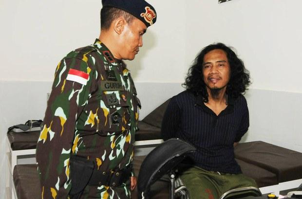 Seorang polisi menjaga tersangka militan MIT Muhammad Basri (kanan) di sebuah rumah sakit militer di Poso, Sulawesi Tengah14 September 2016. [Keisyah Aprilia/BenarNews]