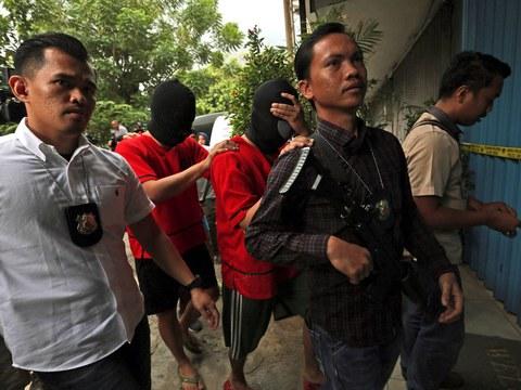 Petugas polisi menggiring para terduga kriminal saat melakukan penggeledahan untuk barang bukti di sebuah tempat di Jakarta yang sering menjadi tempat berkumpulnya kaum lesbian, gay, biseksual, transgender (LGBT), di Jakarta, 9 Oktober 2017.
