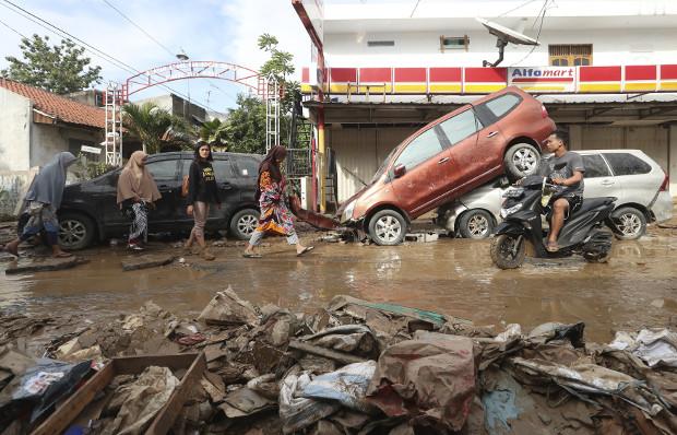 Warga berjalan di dekat kendaraan yang terbawa banjir di Bekasi, Jawa Barat, 3 Januari 2020. AP