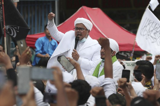 """Dalam foto tertanggal 10 Nopember 2020 ini, Muhammad Rizieq Shihab, pimpinan Front Pembela Islam, kelompok yang secara resmi dibubarkan pemerintah pada 30 Desember 2020 berbicara kepada para pendukungnya, setibanya di Jakarta setelah """"mengasingkan diri"""" di Arab Saudi selama lebih dari tiga tahun. [AP]"""