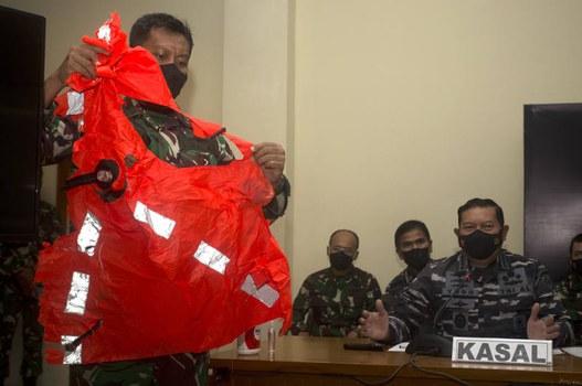 Seorang anggota TNI Angkatan Laut memperlihatkan jaket pengaman yang ditemukan di perairan di sekitar lokasi karamnya kapal selam KRI Nanggala-402, dalam sebuah konferensi pers di Pangkalan TNI AL Ngurah Rai, di Denpasar, Bali, 25 April 2021. [AP]