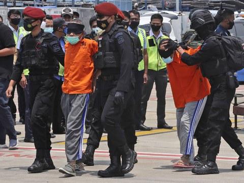 Police mengawal para terduga militan terafiliasi kelompok Jemaah Islamiyah yang ditangkap di Jawa Timur saat ketibaan mereka di Bandara Soekarno-Hatta di Tangerang, 18 Maret 2021.